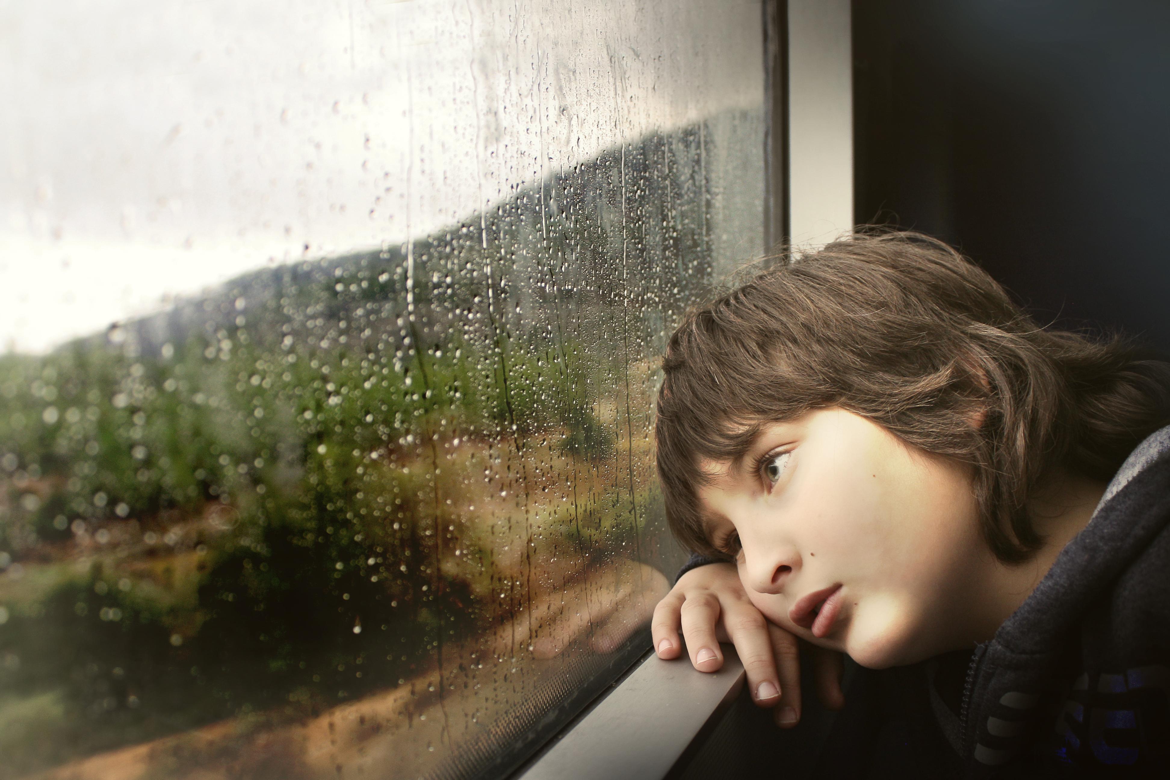 ילד עצוב מביט מהחלון
