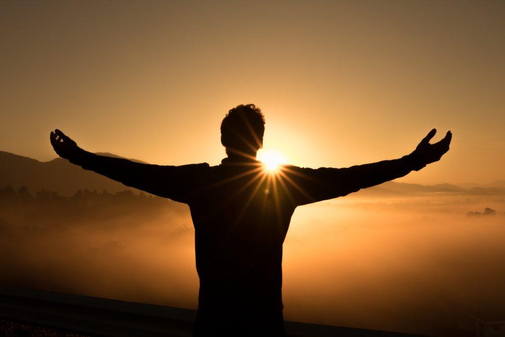 גבר עומד מול השמש עם הידיים פרוסות. גברים מנסים להבין מה מצופה מהם.