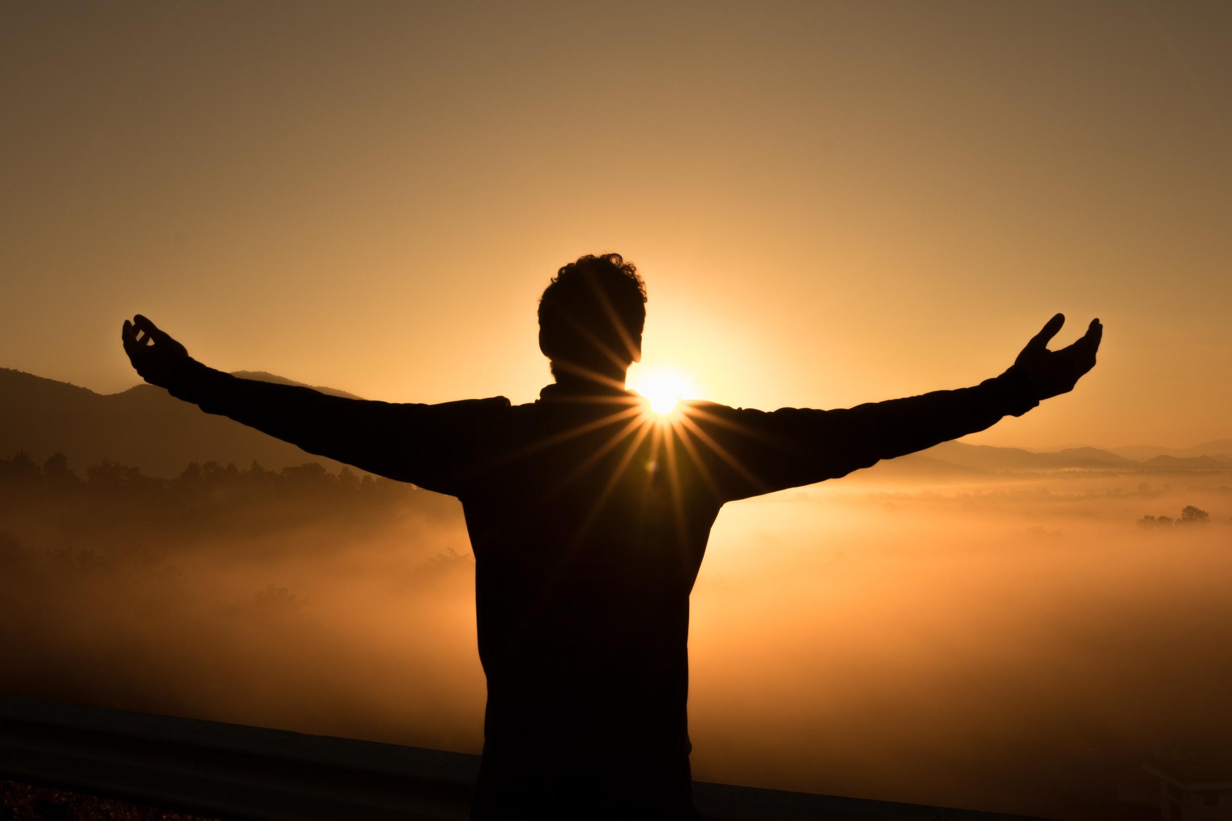 אדם עומד עם זרועות פתוחות אל מול השמש השוקעת