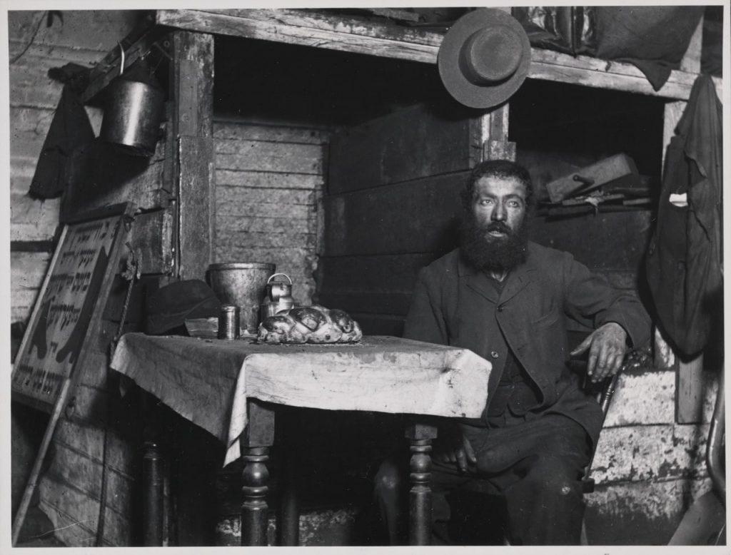 גבר יושב ליד שולחן, גברים משלמים מחיר נפשי על חוסר היכולת לעמוד בציפיות