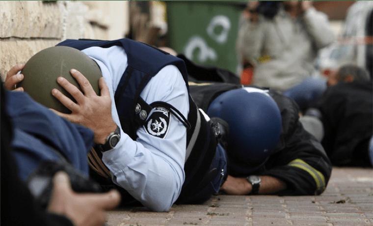 גברים במדים מתכופפים ושוכבים על הרצפה בזמן נפילת טילים