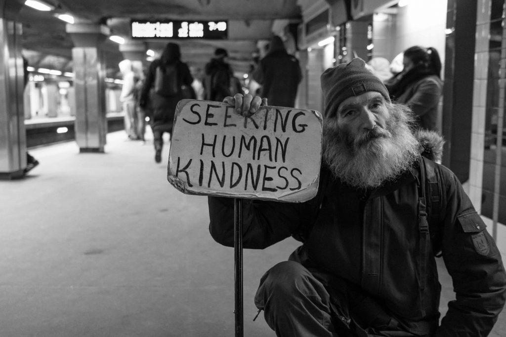 איש מחזיק שלט המבקש אנושיות ואמפטיה
