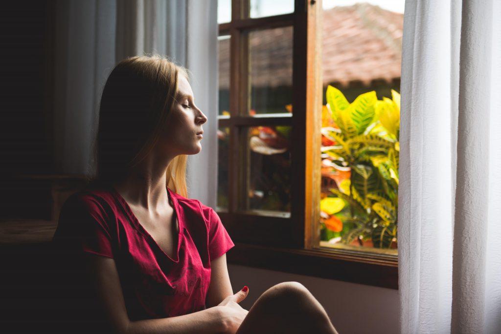 אישה יושבת ועוצמת עיניים. מדיטציה יכולה להיות עזרה נפשית בבידוד