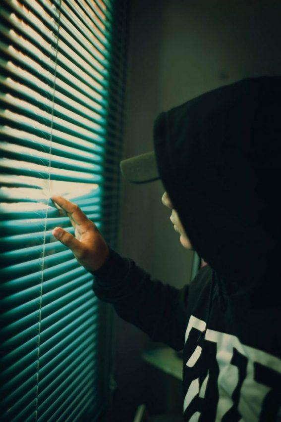 נער בנסיגה חברתית מציץ מתריס בחדרו